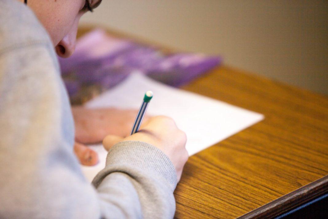 Un écolier en train d'écrire sur sa copie