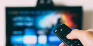 Un homme manipulant sa télécommande devant une télévision