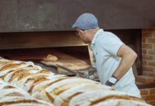 Un boulanger mettant du pain au four.