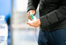 Un homme mettant un peu de gel hydroalcoolique dans sa main.